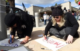 """Alma Trejo, of Montclair, left, and Jessica Alcocer, of Alhambra, make signs as about 200 protestors gather to march through downtown during a """"United Against the Trump Agenda"""" event in Ontario, CA., Saturday, January 21, 2017. (Staff photo by Jennifer Cappuccio Maher/Inland Valley Daily Bulletin/SCNG)"""